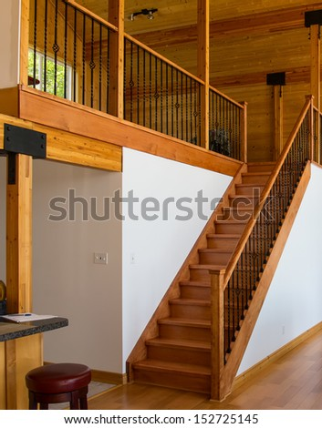 Home interior with wooden staircase leading to the loft - stock photo