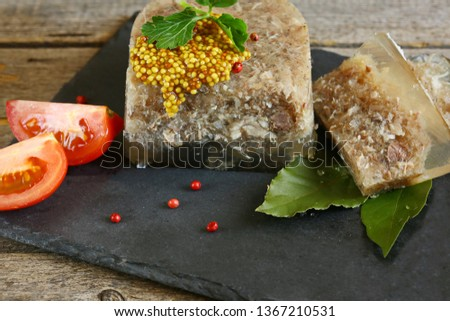 Home jelly, cut into portions lying on a Board on a table of old boards. Near tomatoes, garlic, Bay leaf, parsley. Place for text. The view from the side. Rustic.