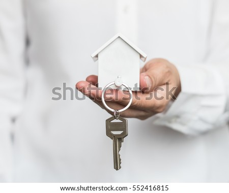 Home key in house keychain on woman person owner's hand support offering security protection awareness concept. Insurance agent in white shirt holding residential key lock/ unlock insure habitat