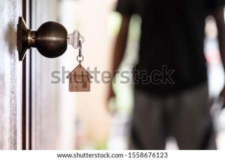 Home key with house keyring in keyhole on wooden door, copy space #1558676123