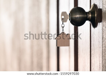 Home key with house keyring in keyhole on wooden door, copy space #1559297030