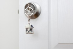 Home key with metal house keychain in keyhole, estate
