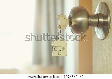 Home key with metal house keychain in keyhole, property concept #1096862462