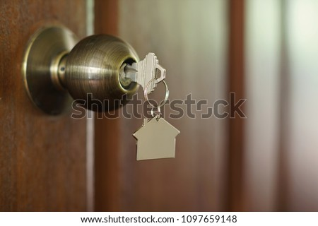 Home key with metal house keychain in keyhole, property concept #1097659148