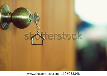 Home key with metal house keychain in keyhole, property concept #1106033348