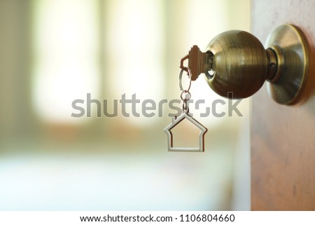Home key with metal house keychain in keyhole, property concept #1106804660