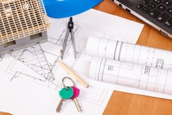 Home keys, electrical diagrams or drawings and accessories for use in engineer jobs lying on desk in office, concept of building home