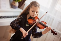 Home lesson for a girl playing the violin. The idea of activities for children during quarantine. Music concept