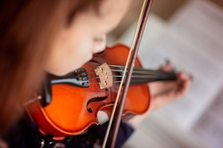 Home lesson for a girl playing the violin. The idea of activities for children during quarantine. Music concept. Selective focus
