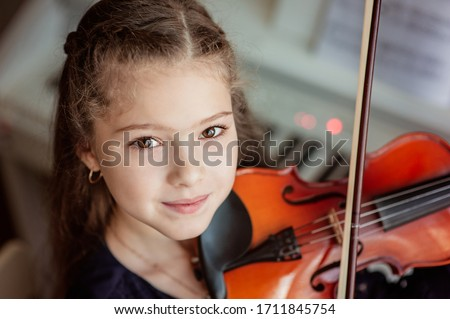 Home lesson for a girl playing the violin. The idea of activities for children during quarantine. Music concept ストックフォト ©