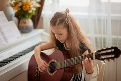 Home lesson on music for a girl with a guitar and piano. The idea of activities for the child at home during quarantine