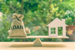 Home loan, reverse mortgage and saving for a real estate concept : House model, loan bag on basic balance scale, depicts saving for a house or flat manageable and turn a home buying dream into reality