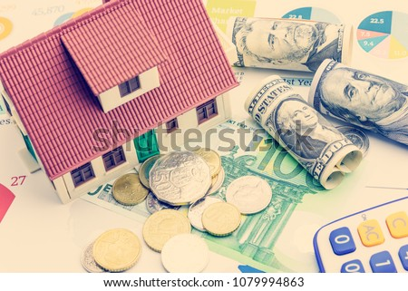 Home loan / reverse mortgage or transforming assets into cash concept : House model on pile of coins, US dollar, EU notes and a calculator, depicts a homeowner or a borrower turns properties into cash