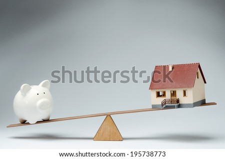 Home loans market. Model house and piggy bank balancing on a seesaw