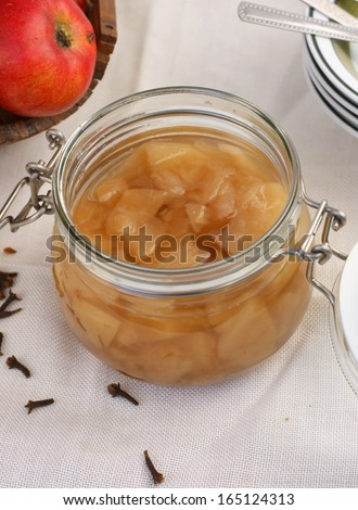 Home made apple compote in a jar (cooked apples in sugar water with spices) on white tablecloth, basket of apples and dried cloves