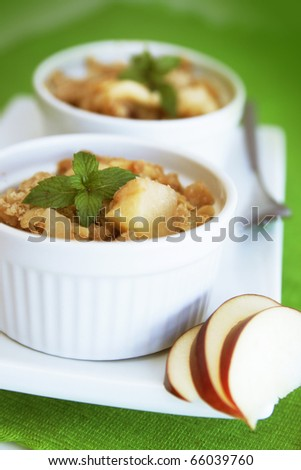Home made apple crumble in a white container on a green background