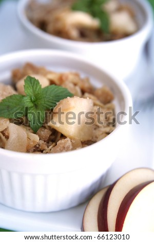 Home made apple crumble in a white container with fresh mint