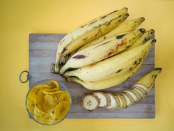 Home made Banana chips with Bunches of ripe yellow plantain/ banana is a most delicious  kerala snack which is made from raw of plantain banana,Isolated on yellow background.