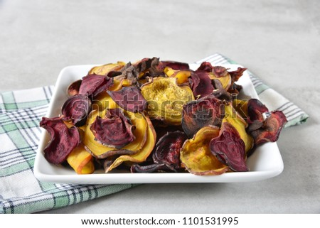Home made beet chips in a small dish on a counter top