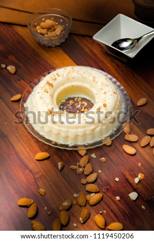 Home made China grass Agar milk pudding dressed with chopped almonds on a wooden rustic table with low light  #1119450206