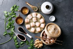 Home made chinese and korean dumplings served on the traditional steamer and bamboo mat decorated with soy sauce, parsley, giner and green tea. Top View