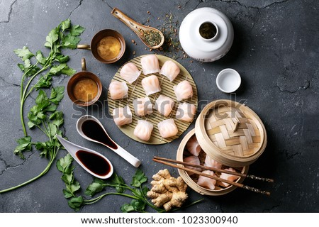 Home made chinese and korean dumplings served on the traditional steamer and bamboo mat decorated with soy sauce, parsley, giner and green tea. Top View ストックフォト ©