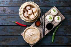 Home made chinese dumplings served on the traditional steamer decorated with sweet chili sauce, fresh chillies and bok choi. Top View
