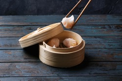 Home made chinese dumplings served on the traditional steamer over blue wooden background. Top View
