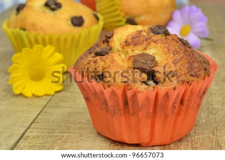 Home made chocolate chip muffins on a wooden board