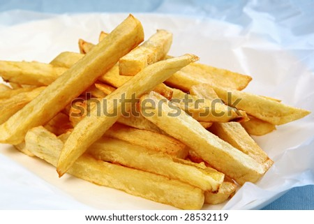 Home-made fat potato chips or french fries, on white paper.
