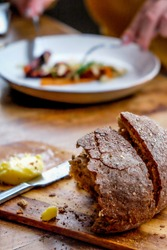 Home made fresh bread and butter on a wooden bread board and table in a restaurant, slightly out of focus in the background are hands holding a knife and fork eating a plate of fine dining food