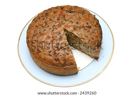 Home made fruit cake with a slice missing, isolated on a white background.