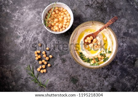 Home made hummus bowl, decorated with boiled chickpeas, herbs and olive oil over a rustic metal background. Top View. #1195218304