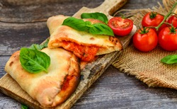 Home made italian calzone vegetarian  pizza with  tomatoes, mozzarella and parmesan cheese and fresh basil