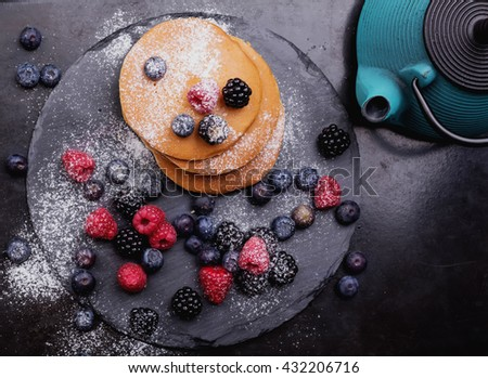 Home made pancakes with berries on metal frying pan decorated with berries (blueberries, raspberries and blackberries). Top View #432206716