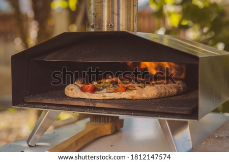 Home made pizza is inserted in a portable aluminium home oven for pizzas. Delicious pizza is baking in an oven, visible fire in the back of the furnace.