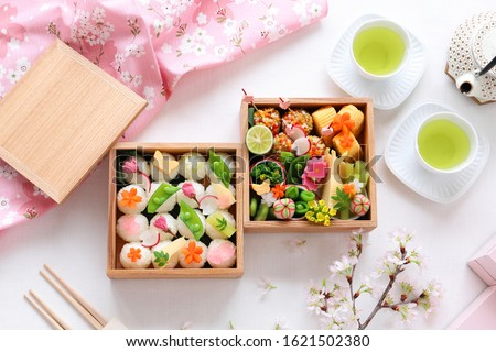 Home made spring bento. Rice balles with vegitables topping  in plain wooden lunch boxes for cherry-blossom viewing.