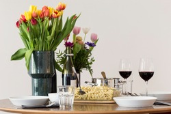 Home-made Swabian Spaetzle (German Spätzle) in transparent glass serving dish, on a set table with tulips and other flowers, and red wine served on tall wine glasses. Small family meal for Sunday
