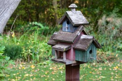 Home made wooden bird house on a pole.