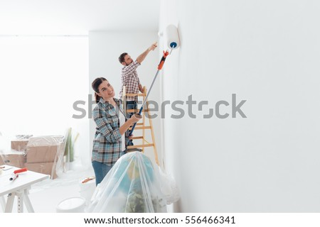 Shutterstock Home makeover and renovation: young happy couple painting their new house interiors using paint rollers
