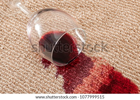 Home mishap and domestic accident concept with close up of  a spilled glass of red wine on brown carpet #1077999515