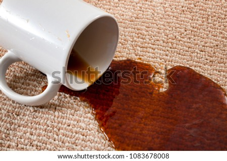 Home mishap, stained carpet, and domestic accident concept with close up of a spilled cup of coffee leaving a stain on the brown carpet #1083678008