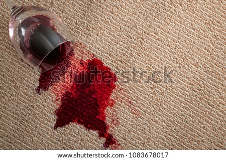 Home mishap, stained carpet and domestic accident concept with top view of  a spilled glass of red wine leaving a stain on the brown carpet with copy space #1083678017