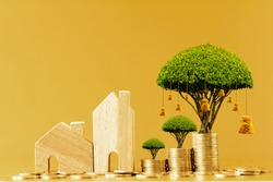 Home model and stack gold coin with growing value and money bag of tree as destinations put on the table in the office, Business investment and loan for real estate or buy house concept.