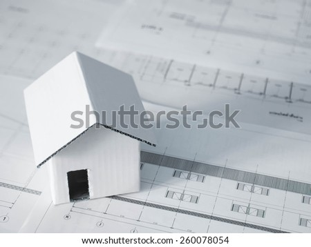 Home model over blurred  architectural blueprint of office building
