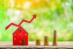 Home model with red arrow graph with growing value and three stack gold coin put on the wood in the public park, Business investment the real estate concept.