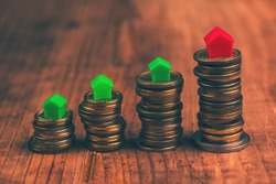 Home mortgage concept with small plastic house models on top of stacked coins.