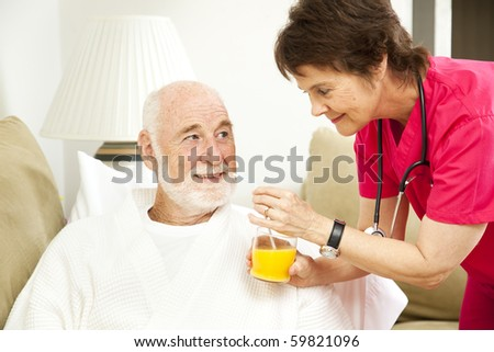 Home nurse giving her elderly patient a glass of orange juice.