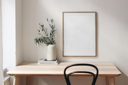 Home office concept. Old books, empty vertical wooden picture frame mockup hanging on white wall. Wooden desk, table. Vase with olive branches. Elegant working space. Scandinavian interior design.