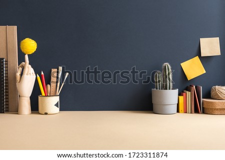 Home office, creative, surreal workspace with cactus, wooden hand and empty blue wall for copy space. Homeschooling workplace. Creative desk.